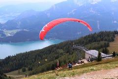 St Gilgen, Austria: L'aliante rosso comincia il suo volo sopra le montagne Fotografie Stock Libere da Diritti