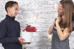 St Giorno del biglietto di S Giovane ragazzo che dà i fiori rossi alla sua amica Fotografie Stock Libere da Diritti
