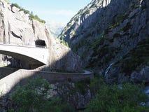 St. Gotthard und Teufelsbruecke, alpine Teufel ` s Straßenbrücke und -tunnel über Reuss-Fluss nahe Andermatt-Stadt, die Schweiz Stockfotografie
