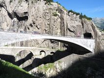 St. Gotthard und Teufelsbruecke, alpine Teufel ` s Straßenbrücke und -tunnel über Reuss-Fluss nahe Andermatt-Stadt, die Schweiz Lizenzfreies Stockbild