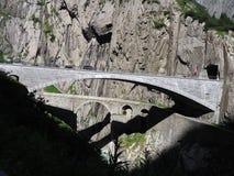St. Gotthard und Teufelsbruecke, alpine Teufel ` s Straßenbrücke und -tunnel über Reuss-Fluss nahe Andermatt-Stadt, die Schweiz Stockfotos