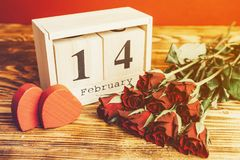 St het minimale concept van de valentijnskaartendag op houten achtergrond Rode rozen en houten caledar met 14 februari op het Stock Foto