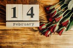 St het minimale concept van de valentijnskaartendag op houten achtergrond Rode rozen en houten caledar met 14 februari op het Stock Foto's