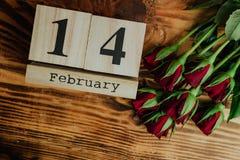 St het minimale concept van de valentijnskaartendag op houten achtergrond Rode rozen en houten caledar met 14 februari op het Royalty-vrije Stock Foto