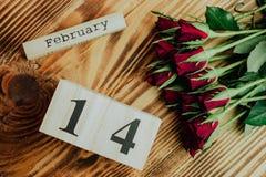 St het minimale concept van de valentijnskaartendag op houten achtergrond Rode rozen en houten caledar met 14 februari op het Stock Afbeelding