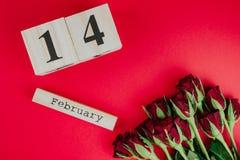 St het minimale concept van de valentijnskaartendag op rode achtergrond Rode rozen en houten caledar met 14 februari op het Stock Afbeeldingen