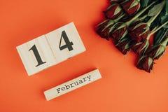 St het minimale concept van de valentijnskaartendag op rode achtergrond Rode rozen en houten caledar met 14 februari op het Royalty-vrije Stock Foto
