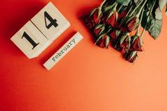 St het minimale concept van de valentijnskaartendag op rode achtergrond Rode rozen en houten caledar met 14 februari op het Stock Fotografie