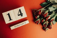 St het minimale concept van de valentijnskaartendag op rode achtergrond Rode rozen en houten caledar met 14 februari op het Stock Foto's