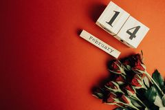 St het minimale concept van de valentijnskaartendag op rode achtergrond Rode rozen en houten caledar met 14 februari op het Royalty-vrije Stock Afbeelding