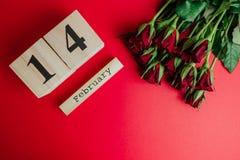 St het minimale concept van de valentijnskaartendag op rode achtergrond Rode rozen en houten caledar met 14 februari op het Stock Afbeelding