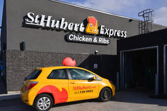 St Hubert store and delivery car. Ottawa, Canada - April 2, 2016:  Delivery car behind St. Hubert, the Quebec based casual dining restaurant chain that was Royalty Free Stock Image