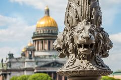 St Isaac& x27; cattedrale di s sfuocato, nella priorità alta la scultura dei leoni su un palo, St Petersburg, Russia fotografia stock libera da diritti