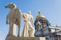 St. Isaac`s Cathedral, in the foreground a sculpture of a male warrior with a horse in Saint-Petersburg stock photography