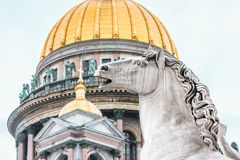 St. Isaac`s Cathedral gold dome and statues of stone horse. Stock Image