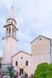 St Ivan's Cathedral. BUDVA, MONTENEGRO - JULY 15, 2014: The facade of the medieval St Ivan's Cathedral with the slender bell tower, located in the old town stock photography