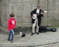 St Ives Cornwall, UK - April 13 2018: Den unga pojken som går förbi en busker som spelar en banjo på en sten, walled gatahörnet arkivfoto