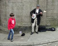 St Ives, Cornwall, UK - April 13 2018: Young boy walking past a busker playing a banjo on a stone walled street corner.  Stock Photo