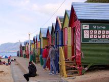 St James Beach Huts. The colourful cabins on the beach of St James in Cape Town, South Africa with the St James sign and people stock photos