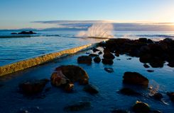 St. James - Dawn Splash Against Tidal Pool. Early morning (dawn) image of a wave splashing against the tidal pool in St. James, Western Cape, South Africa. The royalty free stock image