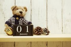 1st January Months wooden calendar Happy New Year background. Happy New Year background 1st January Months wooden calendar with teddy bear and pine cone royalty free stock image