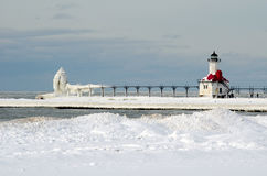 St Joe light house in Winter. The water, the wind, and the cold winter weather has created beautiful icy structures to view on the shores of Lake Michigan in St Stock Image
