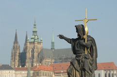 St. John the Baptist Statue Prague. Statue of St. John the Baptist on the Charles Bridge in Prague, Czech Republic overlooks the St. Vitus Cathedral of the royalty free stock images