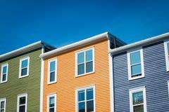 St John, casas de fileira de Terra Nova contra o céu azul imagem de stock