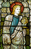 St John the Evangelist stained glass window. Victorian stained glass window showing the Apostle St. John the Evangelist holding a chalice containing a winged Stock Photo