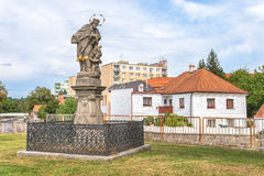 St. John of Nepomuk at Rokycany. Photograph of a statue of St. John of Nepomuk, a religious figure at Rokycany in Czech Republic against a cityscape backdrop Stock Photos