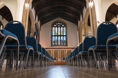 St John's Church hall. Cambridge, UK - March 25, 2015: St John's Church. A Symmetry Old Church Hall Shot with Blue Chairs arranged for assembly stock photos