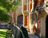 St John's College, Cambridge, England. View of St John's College, Cambridge, England with narrow footpath, bordered by iron railing and small park, historic Royalty Free Stock Images