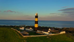 Aerial sunset The St. John`s Point Lighthouse in Northern Ireland stock footage