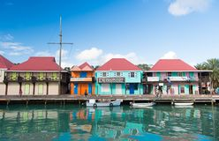 St johns, Antigua - March 05, 2016: boats docked in sea at village quay with houses on blue sky. Summer vacation on. Tropical island. Discovery and adventure royalty free stock photos