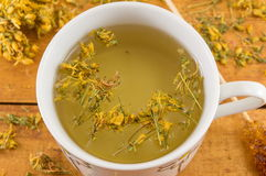 St Johns wort tea and surrounded by dried plants Stock Photos
