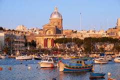 St Joseph church in Kalkara, Malta. The view of  St Joseph church on the shore and a traditional maltese boats (Luzzu) in the Kalkara bay between Birgu and Royalty Free Stock Images