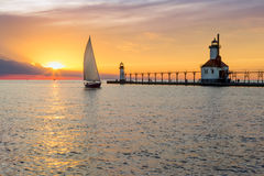 St. Joseph Lighthouse and Sailboat Solstice Sundown. A sailboat rounds the breakwater near sunset on the longest day of the year by the Lighthouses at St. Joseph Royalty Free Stock Photos