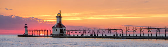 St. Joseph Lighthouses Sunset Panorama. On the Summer Solstice, the sun sets on Lake Michigan between the Inner and Outer North Pier Lighthouses at St. Joseph Stock Photos