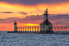 St. Joseph Sunset. The St. Joseph, Michigan North Pier Inner and Outer Lighthouse shine their lights backed by a dramatic and colorful sunset on Lake Michigan Royalty Free Stock Photo