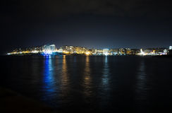 St Julian`s Bay at night, Malta. ST. JULIAN`S - MALTA, 29 March 2017: Lights and reflections in St Julian`s Bay in evening. Saint Julian`s is a town in the Royalty Free Stock Photos