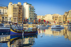 St.Julian`s, Malta - Colorful Luzzu fishing boats at Spinola bay. At sunrise Stock Photos