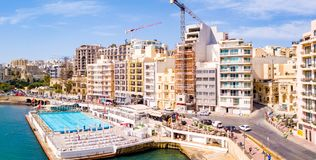 Aerial view on the Spinola Ba. ST.JULIAN`S, MALTA, MAY 15, 2018 - Aerial view on the Spinola Bay with outside pool in St.Julian`s from above - St.Julian`s, Malta Stock Photos
