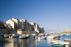 St. julian's malta overdevelopment. Malta maltese luzzu fishing classic fishing boats in harbor st. julian's paceville sliema overdevelopment condominiums Stock Photo