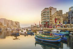 St.Julian`s, Malta - Traditional colorful Luzzu fishing boats at Spinola bay. At sunrise Royalty Free Stock Photo