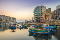 St.Julian`s, Malta - Traditional colorful Luzzu fishing boats. At Spinola bay at sunrise Royalty Free Stock Image