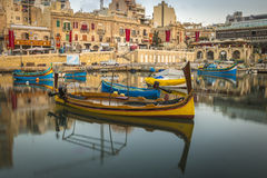 St.Julian`s, Malta - Traditional colorful Luzzu fishing boats. At Spinola bay at sunrise Royalty Free Stock Photos