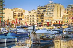 St.Julian`s, Malta - Traditional Luzzu fishing boats at Spinola. Bay at sunrise Royalty Free Stock Photo