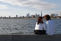 St Kilda Pier. Couple siting on the St Kilda Peir with the Melbourne skyline in the background royalty free stock image