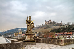 St. Kilian. Statue of St. Kilian on a bridge above the river Main, with castle in the background Stock Image