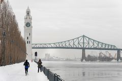 St. Lawrence River with Clock tower in Old Montreal, in winter. Montreal, CA - 21 February 2019: St. Lawrence River, Clock tower and Jacques Cartier Bridge in royalty free stock photos